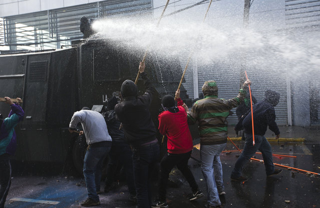 Hooded protesters attack a police water canon near Congress where President Michelle Bachelet was presenting the state-of-the-nation report, in Valparaiso, Chile, Saturday, May 21, 2016. The anti-government protest began as a peaceful march but turned rough as some demonstrators threw rocks at police and gasoline bombs at buildings, resulting in the death of one man who reportedly died of asphyxiation. (AP Photo/Esteban Felix)