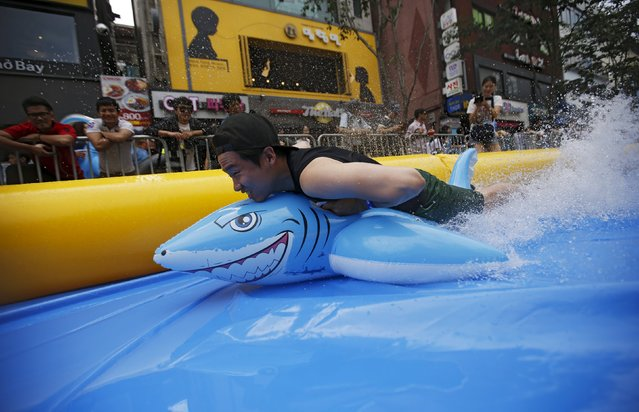 A man on a shark-shaped float enjoys a ride on a 350-meter (1148 feet) long water slide during 2015 City Silde Festa in central Seoul, South Korea, July 19, 2015. A 350 meter-long waterslide has been installed in downtown of Seoul, the longest waterslide to be recorded in Korea, according to local media. (Photo by Kim Hong-Ji/Reuters)
