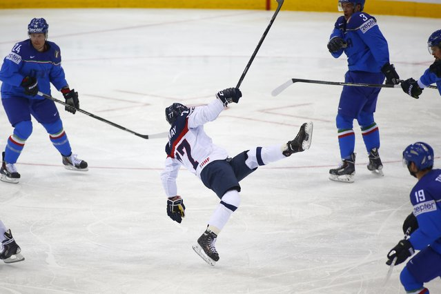 Slovakia's Martin Reway, center, falls during the Group A preliminary round match against Italy at the Ice Hockey World Championship in Minsk, Belarus, Saturday, May 17, 2014. (Photo by Sergei Grits/AP Photo)