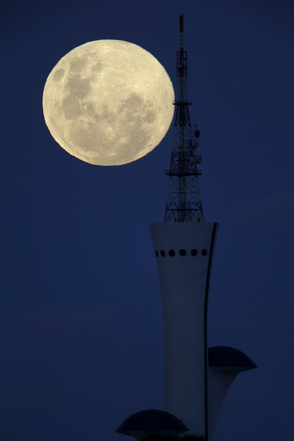 The full moon rises over the Brasilia Digital TV Tower during a celebration of Brasilia's 56th anniversary in Brasilia, Brazil April 21, 2016. (Photo by Ueslei Marcelino/Reuters)