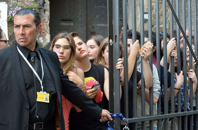 Fans gather as guests arrive at Forte di Belvedere in Florence. The couple and their guests flew out of the City of Light aboard private jets and arrived midday in the historic Italian city. (Photo by Tiziana Fabi/AFP Photo)
