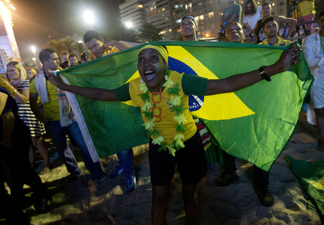 Brazilian fan Regina De Cristo celebrates the second goal against Croatia as she watches the World Cup opener on a giant screen during the FIFA Fan Fest on Copacabana beach in Rio de Janeiro, Brazil, Thursday, June 12, 2014. After taking the early lead in the opening match of the international soccer tournament, Croatia fell 3-1 to the five-time champion Brazil. (Photo by Silvia Izquierdo/AP Photo)
