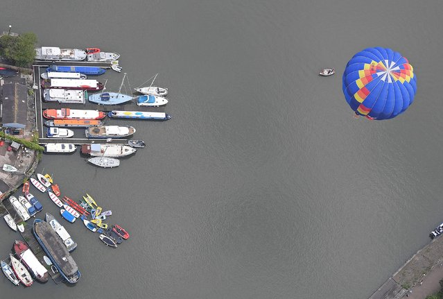 A balloon flies over moored boats during a mass take off at the annual Bristol hot air balloon festival in Bristol, Britain, August 8, 2019. (Photo by Toby Melville/Reuters)