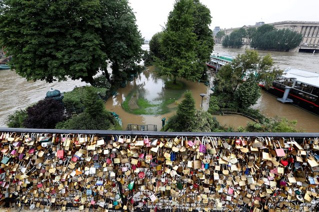"""Padlocks clipped by lovers are seen in front of the """"Ile de la Cite"""" flooded by the River Seine in central Paris, France, June 1, 2016. (Photo by Charles Platiau/Reuters)"""