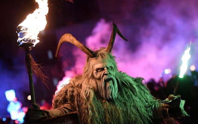 A participant wearing a traditional Krampus costume and a mask performs during a Krampus run in the village of Biberwier, Austria on November 30, 2019. (Photo by Angelika Warmuth/Reuters)