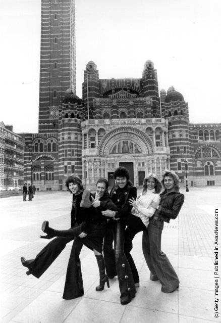 1976: Pop singer Alvin Stardust, centre, with members of the singing dance troupe 'Guys And Dolls' outside Westminster Cathedral, London, where they have been rehearsing for a concert