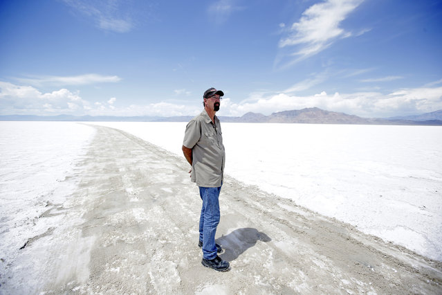 In this Tuesday, July 21, 2015, photo, Wendover Mayor Mike Crawford stands along the exposed mud track on the Bonneville Salt Flats, in Utah. (Photo by Rick Bowmer/AP Photo)
