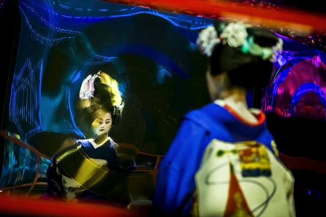 A Maiko, an apprentice geisha, is reflected in a warped mirror as she performs a traditional dance in front of a tank with goldfish at the Art Aquarium exhibition in Tokyo July 27, 2015. (Photo by Thomas Peter/Reuters)