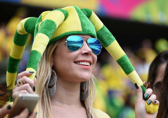 A Brazilian fan with a fancy hat smiles prior to a Group A football match between Brazil and Mexico in the Castelao Stadium in Fortaleza during the 2014 FIFA World Cup on June 17, 2014. (Photo by Vanderlei Almeida/AFP Photo)