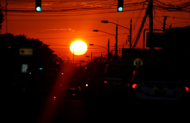 Cars drive on a road during sunset in San Jose, Costa Rica February 20, 2017. (Photo by Juan Carlos Ulate/Reuters)