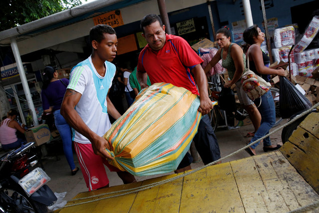 Men carry a bag filled with staple items in front of a store in Puerto Santander, Colombia, June 3, 2016. (Photo by Carlos Garcia Rawlins/Reuters)