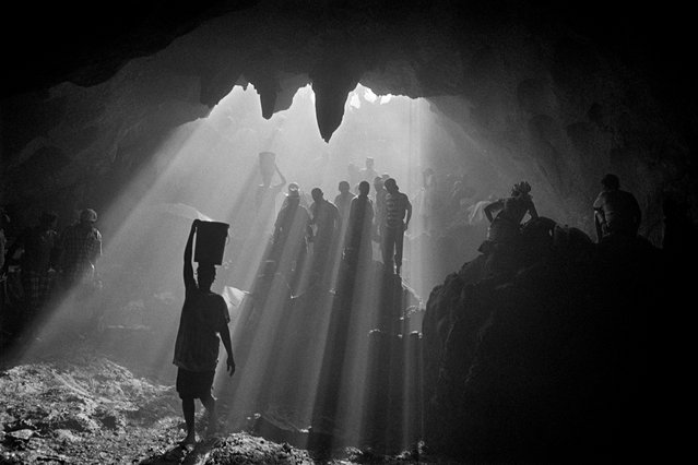 "Artibonite region, Haiti, 2001. Saint Francis of Assisi's cave. Cristina Garcia Rodero writes: ""It's that magical moment of kismet when space, time, wisdom and heart mingle and produce a unique photograph full of expression; where composition, timing, experience and emotion come together perfectly to create this sparkle of an image full of life and soul. Here, the rays of light of the sunset illuminate the darkness of the cave, caressing the bodies of pilgrims and defining their silhouettes in a harmony of faith and nature"". (Photo by Cristina Garcia Rodero/Magnum Photos)"