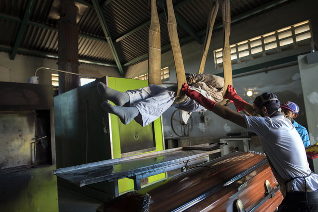 Cemetery workers lift a corpse from a coffin to a metal plate as they prepare the body for cremation at a cemetery in Maracaibo, Venezuela, November 27, 2019. Some overcome the financial burden of a relative's death by renting caskets, a cheaper option than buying one. (Photo by Rodrigo Abd/AP Photo)