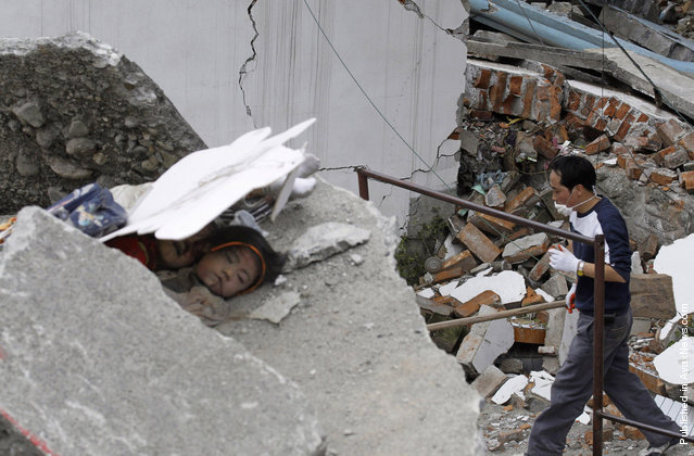 A father looking for his child walks past two dead girls who are buried among the ruins of a destroyed primary school in the old city district, near a mountain at the earthquake-hit Beichuan county, Sichuan province, May 15, 2008