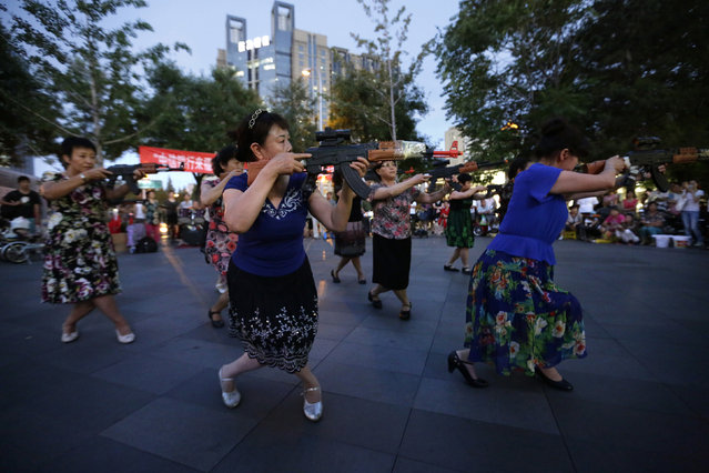 "Chinese women holding toy guns dance to a revolutionary song as part of their daily exercise at a square outside a shopping mall in Beijing, June 27, 2014. About 30 local residents formed this ""Nanguan"" art group that enjoys performing and dancing to revolutionary songs as part of their nightly fitness activity. (Photo by Jason Lee/Reuters)"
