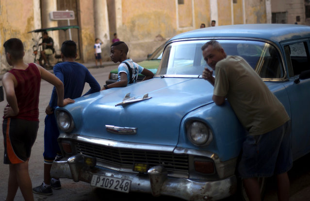Pedestrians lean against an American classic car as they wait for traffic to pass in Old Havana, Cuba, Tuesday, February 17, 2015. (Photo by Ramon Espinosa/AP Photo)