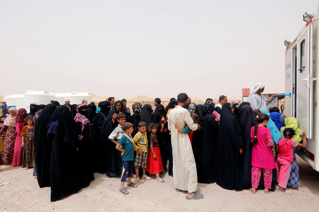 Displaced people, who fled from Falluja because of Islamic State violence, stand in line for treatment at a refugee camp in Ameriyat Falluja, south of Falluja, Iraq, June 16, 2016. (Photo by Ahmed Saad/Reuters)