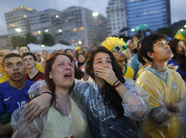 Brazil soccer fans cry as they watch their team play a World Cup semifinal match against Germany on a live telecast inside the FIFA Fan Fest area on Copacabana beach in Rio de Janeiro, Brazil, Tuesday, July 8, 2014. (Photo by Leo Correa/AP Photo)