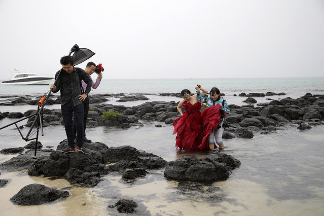 A Chinese couple from Yunnan accompany a photographer as they make their way through the water and on the rocks for a wedding photo session at the Cap Malheureux beach on the Indian Ocean island Mauritius, August 5, 2015. (Photo by Jacky Naegelen/Reuters)