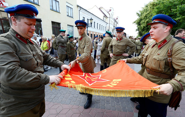Military enthusiasts dressed as World War Two Red Army soldiers hold a flag as they mark the 75th anniversary of the Nazi Germany invasion, in Brest, Belarus June 21, 2016. (Photo by Vasily Fedosenko/Reuters)