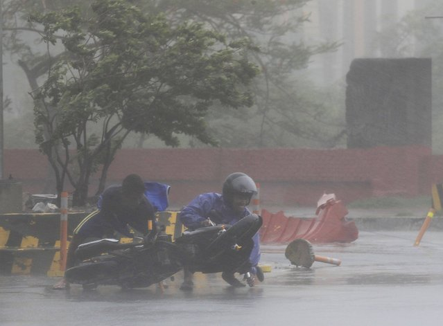 A man assisted a motorcyclist after he fell along a main road after strong winds brought by Typhoon Rammasun, locally called Glenda, battered the capital, metro Manila July 16, 2014.  Philippine authorities evacuated almost 150,000 people from their homes and shuttered financial markets, government offices, businesses and schools on Wednesday as typhoon Rammasun gathered strength and hit the capital, Manila. (Photo by Romeo Ranoco/Reuters)