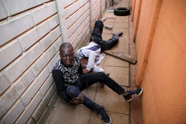 A suspect (R) writhes in pain as he is handcuffed to his accomplice after he was shot while they attempt to break into a house belonging to a police officer couple, in the south of Johannesburg, August 12, 2015. Local media reported a rise in robbery and housebreaking incidents in Johannesburg. (Photo by Siphiwe Sibeko/Reuters)