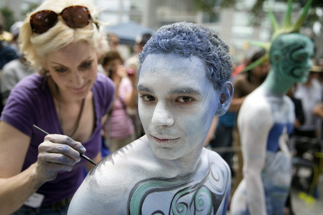 Crist Crow is painted at Columbus Circle as body-painting artists gathered to decorate nude models as part of an event featuring artist Andy Golub, Saturday, July 26, 2014, in New York. Golub says New York was the only city in the country that would allow his inaugural Bodypainting Day. (Photo by John Minchillo/AP Photo)