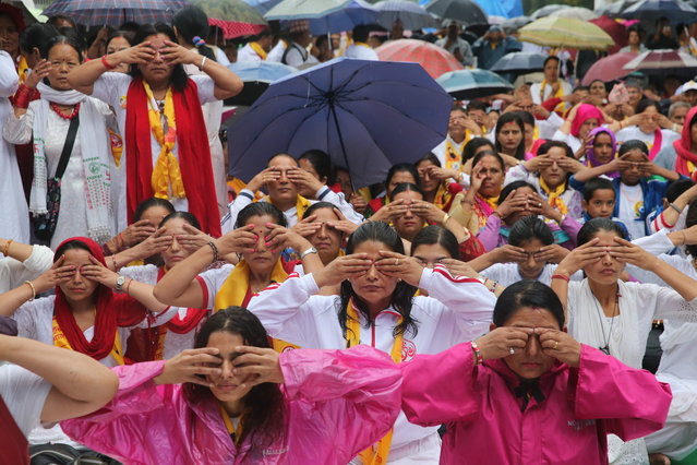 People practise yoga in the rain on the International Yoga Day on June 21, 2017 in Kathmandu, Nepal. Nepal's Prime Minister Sher Bahadur Deuba and people do yoga in the rain to celebrate the International Yoga Day in Kathmandu. (Photo by Zhang Chenyi/China News Service/VCG via Getty Images)