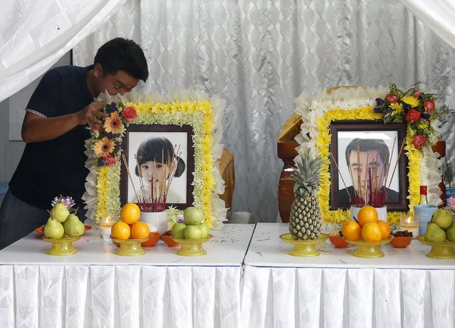 A family member places photographs of 4-year-old Lee Jing Xuan and her father Lee Tze Siang in front of their coffins, after they were killed in Monday's deadly blast in Bangkok, Thailand, at their home in Butterworth, Malaysia, August 20, 2015. (Photo by Olivia Harris/Reuters)