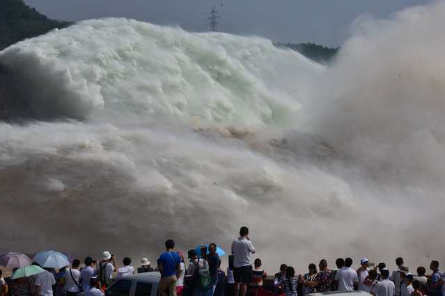 Visitors watch as water gushes from a section of the Xiaolangdi Reservoir on the Yellow River, in Luoyang, Henan Province, China, June 29, 2016. (Photo by Reuters/Stringer)