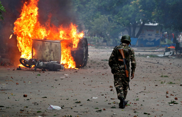 A member of the security forces walks towards a burning vehicles during violence in Panchkula, India, August 25, 2017. (Photo by Cathal McNaughton/Reuters)