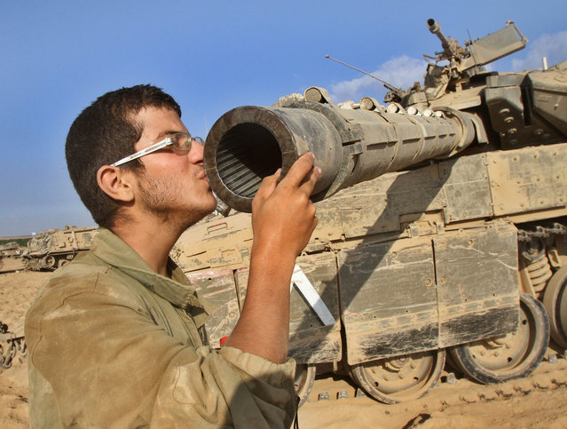 An Israeli soldier kisses his  Merkava tank along the border between Israel and the Gaza Strip after he pulled out from the Gaza Strip  on August 3, 2014. At least 10 people died in a fresh strike on a UN school in Gaza shortly after Israel confirmed it had begun withdrawing some troops from the war-torn enclave. (Photo by Gil Cohen Magen/AFP Photo)