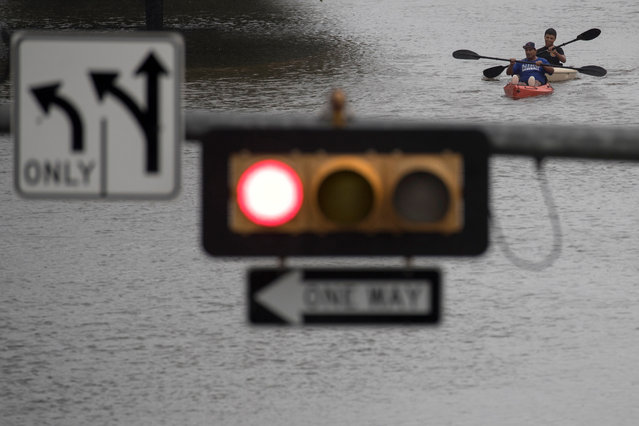 Men use kayaks to get through an intersection in Pearland, in the outskirts of Houston, Texas on August 27, 2017. (Photo by Adrees Latif/Reuters)
