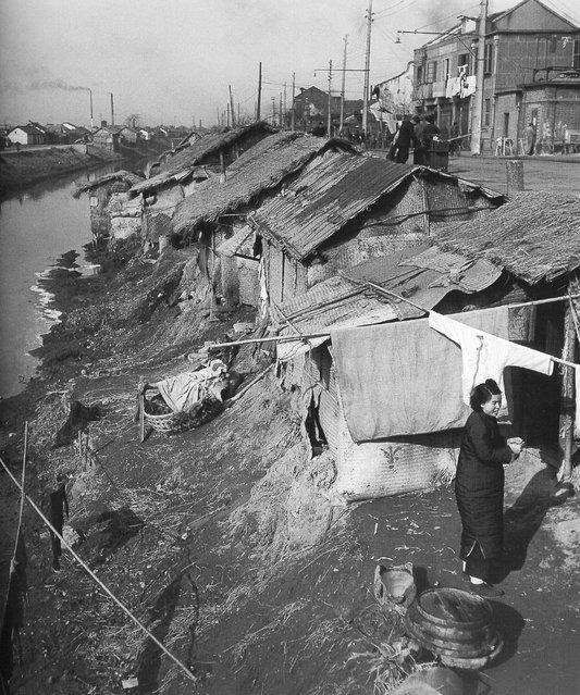 1947年12月,在河边贫民窟凉晒衣服的女人 (In December 1947 the riverside slum woman Liangshai clothes)