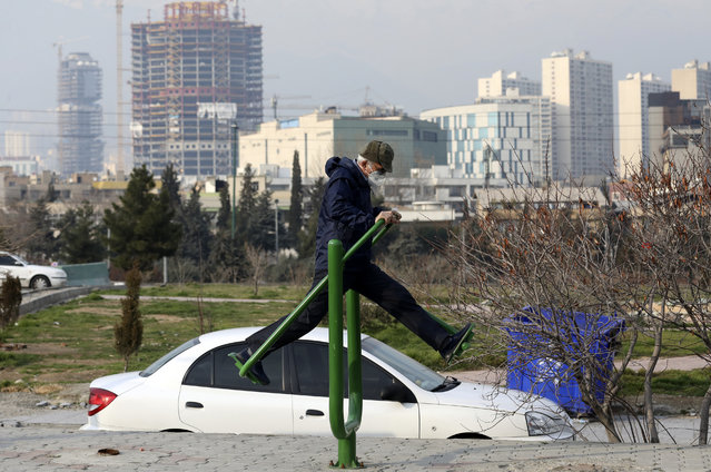 A man with a mask exercises as he spends his weekend afternoon at Pardisan Park in Tehran, Iran, Friday, February 28, 2020. (Photo by Vahid Salemi/AP Photo)