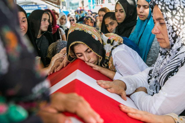 "A woman lays her head on the coffin of a victim of the failed July 15 coup attempt during his funeral in Istanbul on July 17, 2016. Turkish President Recep Tayyip Erdogan vowed Sunday to purge the ""virus"" within state bodies, during a speech at the funeral of victims killed during the coup bid he blames on his enemy Fethullah Gulen. (Photo by Gurcan Ozturk/AFP Photo)"