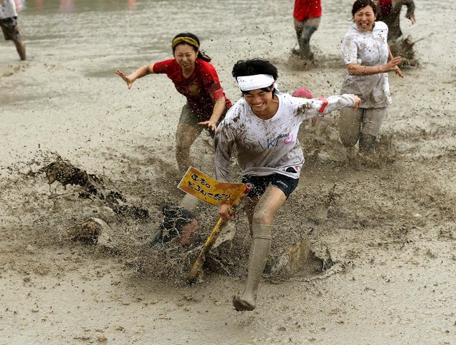 Festival-goers run through the mud to grab  the winning flag during the village mud festival in Himeji, Japan, on August 17, 2014. (Photo by Buddhika Weerasinghe/Getty Images)