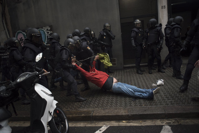 Riot police drag a member of the public away from a school being used as a polling station for the banned referendum, in Barcelona, Spain, on Sunday, October 1, 2017. Spanish police moved in to shut down some polling stations as voting began Sunday in Catalonias illegal referendum on independence. (Photo by Geraldine Hope Ghelli/Bloomberg via Getty Images)