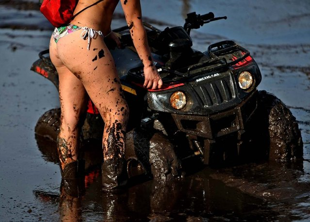Nicole Devlin of Vero Beach wait.for help to get her ATV out of the mud bog. (Photo by Gary Coronado/The Palm Beach Post)