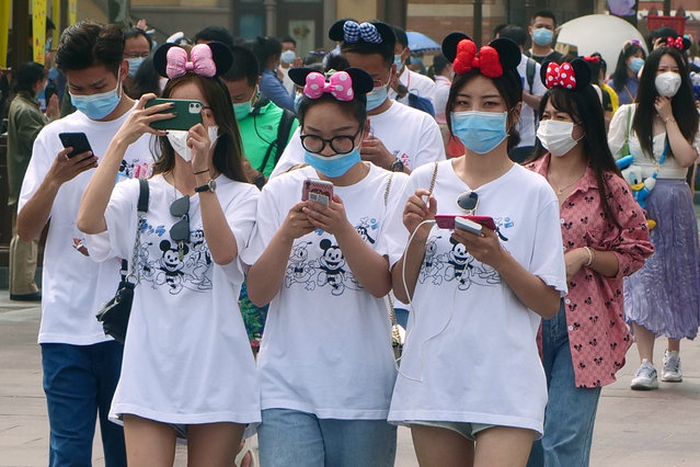Visitors, wearing face masks, enter the Disneyland theme park in Shanghai as it reopened, Monday, May 11, 2020. Visits will be limited initially and must be booked in advance, and the company said it will increase cleaning and require social distancing in lines for the various attractions. (Photo by Sam McNeil/AP Photo)