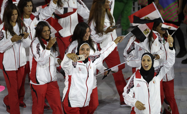 Egyptian athletes take photos with their smartphones as they march into the Maracana stadium during the opening ceremony for the 2016 Summer Olympics in Rio de Janeiro, Brazil, Friday, August 5, 2016. (Photo by Matt Slocum/AP Photo)