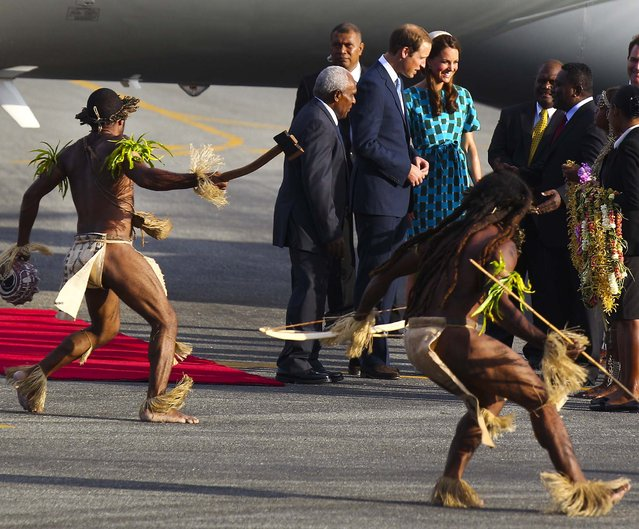 Britain's Prince William and wife Kate, the Duke and Duchess of Cambridge, arrive at Honiara International Airport in Solomon Islands, as warriors in traditional dress dance around them, on September 16, 2012. (Photo by Rick Rycroft/Associated Press)