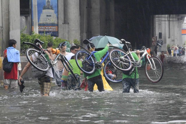 Bikers carry their bicycles as they wade through a flooded street after tropical storm Fung-Wong battered metro Manila September 19, 2014. (Photo by Erik De Castro/Reuters)