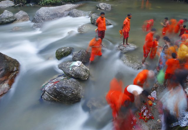 A picture taken with a long shutter shows Nepalese Hindu pilgrims, also known as Bolboms, collecting holy water to worship Lord Shiva, the god of creation and destruction, at the Bagmati river in Kathmandu, Nepal, 08 August 2016. Hindu devotees from all over Nepal and India gathered in the northern holy city Sundarijal, 22 kilometers from Nepal's capital Kathmandu, to collect water that is claimed to be holy. The water is then stored in two small buckets, hanging on colorful wooden sticks and on their body. (Photo by Narendra Shrestha/EPA)