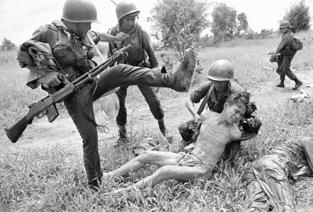 A suspected Vietcong is kicked by a Vietnamese soldier holding a rifle as another soldier attempts to tie his hands on October 22, 1965. The prisoner was one of 15 captured October 21 near Xom Chua when government troops raided in the plain of reeds area. Troops killed 43 suspected Vietcong and seized some arms. (Photo by Richard Merron/AP Photo)