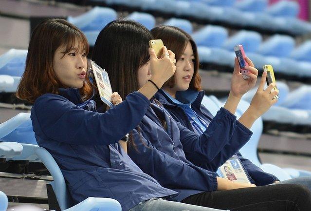 South Korean women take selfies while watching a badminton training session at Gyeyang gymnasium during the 2014 Asian Games in Incheon on September 18, 2014. (Photo by Prakash Singh/AFP Photo)
