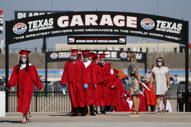 "Ponder High School graduates march out of the garage area and onto the front stretch to participate in their graduation ceremony at Texas Motor Speedway in Fort Worth, Texas, Tuesday, May 19, 2020. Texas Motor Speedway is hosting 30 socially-distanced high school graduation ceremonies over the next few weeks. The first two were Monday night. Students receive their diplomas on the front stretch of the track with family and friends in their cars parked on the infield watching the ceremony on the track's massive ""Big Hoss"" TV screen. (Photo by Tony Gutierrez/AP Photo)"