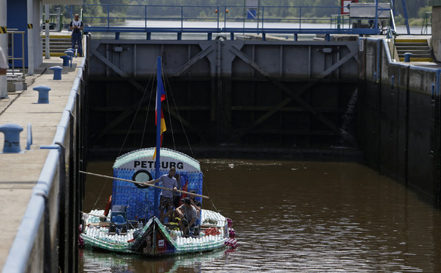 Jan Kara, Jakub Bures, Jan Brand and Jan Holan sit on their boat, made with plastic bottles, as they wait in a lock chamber on the Elbe river near Kostelec nad Labem July 15, 2014. (Photo by David W. Cerny/Reuters)