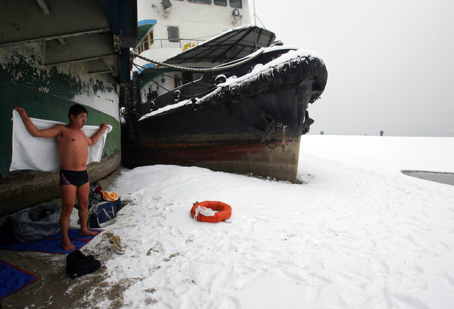 A winter swimmer wipes water on him beside a stranded ship on the beach of the Yangtze River after snow on January 27, 2008 in Wuhan of Hubei Province, China. Measured in Wuhan's Hankou District, the water level of Asia's longest river (about 6,300 km) fell to 13.98 meters, the lowest compared with the same time of year since records began in 1866, affecting shipping, fishery and water supply. (Photo by China Photos)