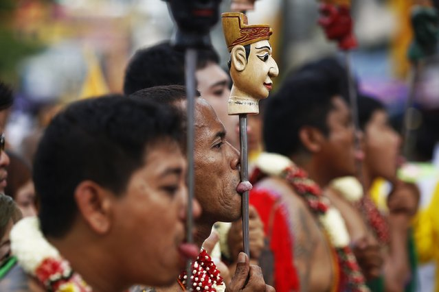 Devotees of the Chinese Bang Neow Shrine with decorated spikes pierced through their tongues, take a part in a procession celebrating the annual vegetarian festival in Phuket September 29, 2014. (Photo by Damir Sagolj/Reuters)